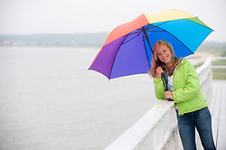 girl holding a rainbow umbrella while standing on a deck by the bay in East Hampton,NY