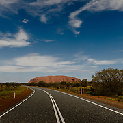 Road leading to Uluru (Ayers Rock or Red Rock) in Northern Territory.