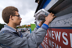 Teenage boy putting old newspapers into a recycling bank,