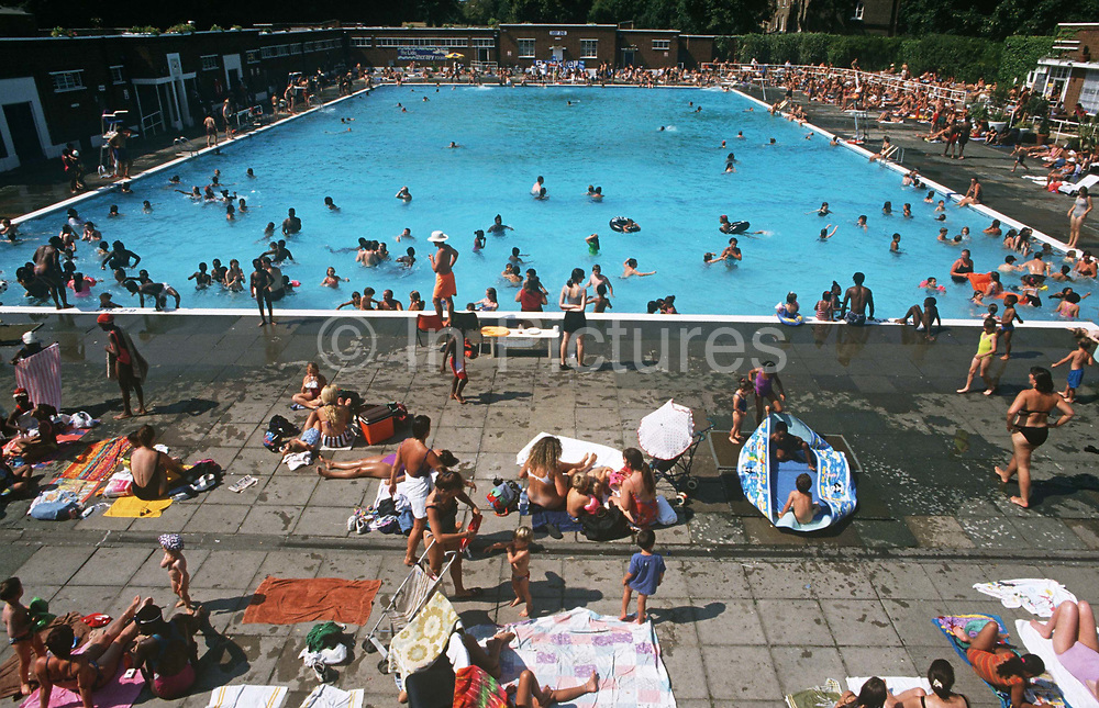 Crowds enjoy the warmth of a summer's heat wave within the confines of  Brockwell (Brixton) Lido. These Londoners have escape the street and unwind during a warm spell of weather and before another day of city heat. They swim and bathe in the chilly waters of this unheated pool. The Lido is a magnet, an oasis, for city dwellers to escape, if only for an hour from the pressures of fast urban life. Many enjoy the benefits of outdoor bathing and the friendship of meeting old friends. In the centre, a mother helps her young daughter up from the cool morning water before another hot day in August. Brockwell Lido is a large, open-air swimming pool in Brockwell Park, Herne Hill, London. It opened in July 1937, closed in 1990 and after a local campaign was re-opened in 1994.