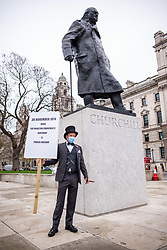 © Licensed to London News Pictures. 30/11/2020. London, UK. A man in a top hat and placard celebrates Winston Churchill's birthday in Parliament Square this morning. The Government has announced a new Covid-19 3 tiered system will come into effect in England on Wednesday 2nd December 2020 marking the end of lockdown with all non-essential shops, leisure centres, swimming pools, gyms and golf courses allowed to reopen again for the Christmas period. Photo credit: Alex Lentati/LNP