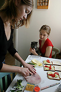 (MODEL RELEASED IMAGE). Delphine Le Moine, a dance student at the Centre International de Danse Jazz Rick Odums, makes lunch at home with her sister Laetitia, a high school student, who holds their cat in the family kitchen in the Paris suburb of Montreuil, France. (Supporting image from the project Hungry Planet: What the World Eats.)