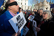 People's Vote supporters wearing blindfolds and carrying placards assembled in Parliament Square for the Blindfold Brexit protest ahead of a crunch debate in the House of Commons to illustrate that this Brexit would provide no clarity and no closure about our future relationship with Europe on 14th February 2019 in London, England, United Kingdom. A woman debates that the protest is pointless with one of the protesters.