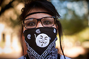 "16 OCTOBER 2011 - PHOENIX, AZ: An Occupy Phoenix protester with a Guy Fawkes pin on her bandana from the movie ""V for Vendetta"" in downtown Phoenix, AZ, Sunday. The Guy Fawkes mask has become the most visible sign of the Occupy movement. About 200 people continued the Occupy Phoenix protest in downtown Phoenix Sunday afternoon. The protest peaked Saturday afternoon at about 2,000 people. Nearly 50 people were arrested late Saturday night on misdemeanor trespassing charges when they tried to camp in a park near downtown and on Sunday the crowd dwindled to 200. Protesters hope to continue the protest through Monday by marching around downtown and picketing banks in the area.   PHOTO BY JACK KURTZ"