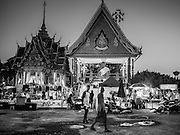 """14 MARCH 2014 - NAKHON CHAI SI, NAKHON PATHOM, THAILAND: People walk through the parking lot at Wat Bang Phra to watch an acrobatic troupe perform at the opening of the temple's tattoo festival. Wat Bang Phra is the best known """"Sak Yant"""" tattoo temple in Thailand. It's located in Nakhon Pathom province, about 40 miles from Bangkok. The tattoos are given with hollow stainless steel needles and are thought to possess magical powers of protection. The tattoos, which are given by Buddhist monks, are popular with soldiers, policeman and gangsters, people who generally live in harm's way. The tattoo must be activated to remain powerful and the annual Wai Khru Ceremony (tattoo festival) at the temple draws thousands of devotees who come to the temple to activate or renew the tattoos. People go into trance like states and then assume the personality of their tattoo, so people with tiger tattoos assume the personality of a tiger, people with monkey tattoos take on the personality of a monkey and so on. In recent years the tattoo festival has become popular with tourists who make the trip to Nakorn Pathom province to see a side of """"exotic"""" Thailand.   PHOTO BY JACK KURTZ"""
