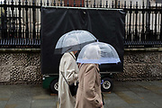 Two ladies use transparent umbrellas during heavy rainfall on an autumn afternoon outside St. Martin-in-the-Fields church on Trafalgar Square, on 24th October 2019, in Westminster, London, England.