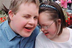 Portrait of teenage boy and girl with Downs Syndrome standing close together,
