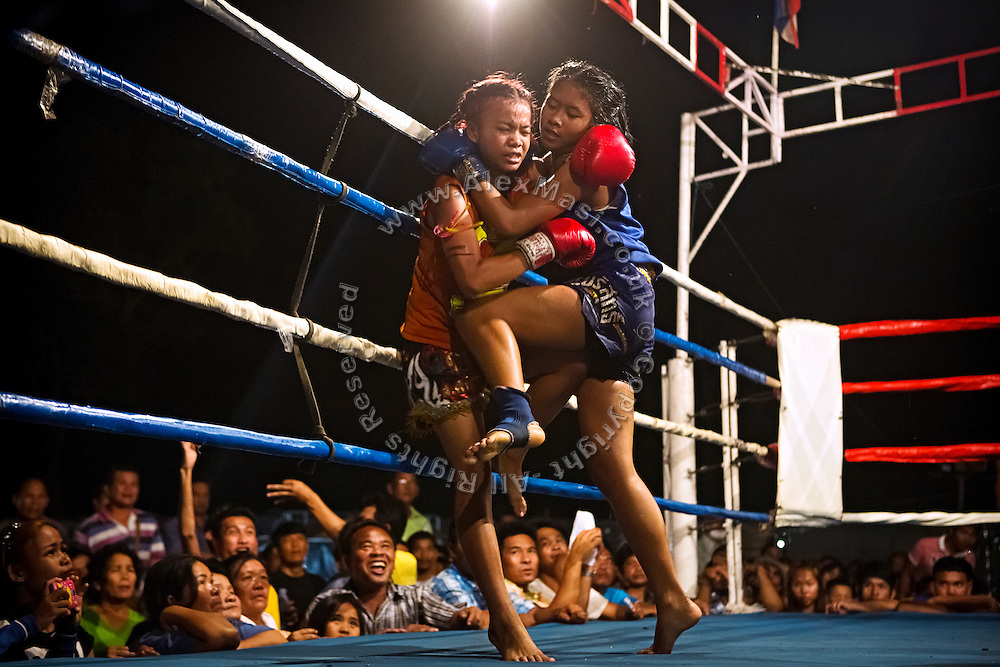 Phatsorn Bunmasen, 14, is hitting her opponent in the stomach using the knee, during a Muay Thai boxing match organised in a village near Ubon Ratchathani, northeast Thailand.