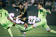 Los Angeles Galaxy forward Juan Pablo Angel, middle, takes a shot as he is challenged by Seattle Sounders FC defender James Riley, left, and Jeff Parke during the second half of an MLS soccer match, Monday, July 4, 2011, in Carson, Calif. The game ended in a 0-0 tie. (AP Photo/Bret Hartman)