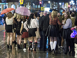 """© Licensed to London News Pictures . 15/12/2012 . Manchester , UK . Crowds in the streets reach for their umbrellas and handbags to shelter from rain . Revellers enjoy a wet but busy night out on one of the last weekends before Christmas , a traditionally busy time when office parties and clubbers decent on bars and clubs , often known as """" Mad Friday """" . Photo credit : Joel Goodman/LNP"""
