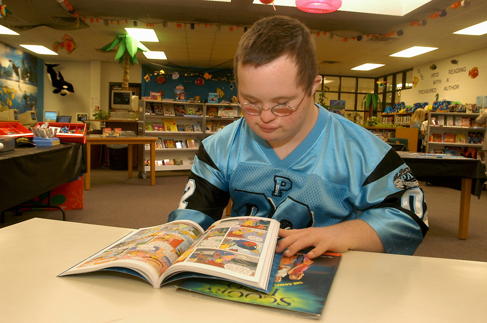 Mabank, Texas September 10, 2003:  Elementary and middle school regular and special education, showing children mainstreamed into regular classrooms, 5th through 7th grades in the Mabank Independent School District. MODEL RELEASES SP-71 to SP-80.   <br /> Thirteen (13) year old boy with Down's Syndrome in the library, looking at book. MODEL RELEASE SP75 (boy in blue) <br /> ©Bob Daemmrich