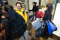 © Licensed to London News Pictures . 26/12/2014 .  Manchester , UK . A woman with numerous handbags on her arm amongst crowds of bargain hunters in Selfridges in Manchester City Centre for the Boxing Day Sale . Photo credit : Joel Goodman/LNP