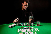 A young male gambler at the gambling table holds a cigar and looks at cards model release available