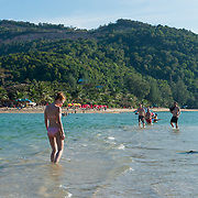People walking from Phangan island to Ko Ma island at low tide shallow water, Thailand