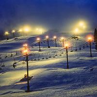 Lights illuminate the slopes for night skiing at Snoqualmie Pass Ski Area in Washington.