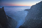 Parmenter Welty leans over the sea wall at twilight for a better view of the spray from the natural blowhole at La Bufadora near Ensenada, Baja California Norte, Mexico.