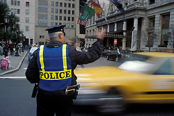 Police officer directing traffic near Plaza Hotel and Central Park entrance, NYC CITY URBAN STOCK PHOTO