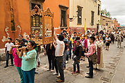 Local residents carry a statue of St Michael ahead of a procession of Mexican cowboys as they ride through the streets of San Miguel de Allende, Mexico.