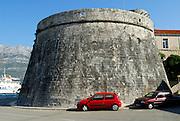 Bright red car parked alongside Large (Velika Knezeva Kula) Prince's or Governor's tower,  Korcula old town, island of Korcula, Croatia.