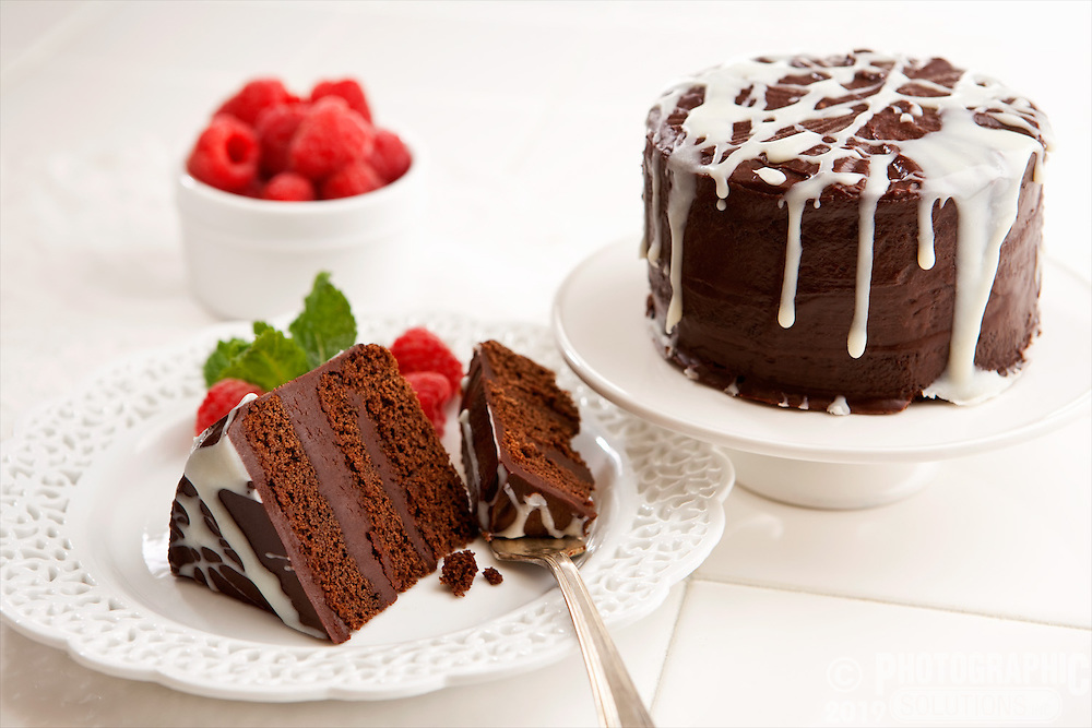 A slice of chocolate cake with strawberries and white sauce