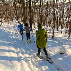 Three women snowshoeing through the forest above Indian Hill Reservoir in West Newbury, Massachusetts.