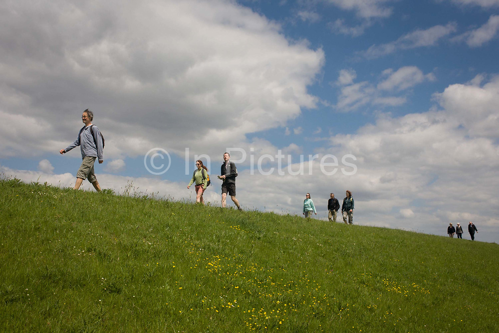 A group of country ramblers walk along the sea defence embankment of Halstow Marshes on the Kent Thames estuary marshes, potentially threatened by the future London airport. With the panoramic views beyond, the walkers stride across the landscape that could controversially become the site for London's estuary airport, built on reclaimed and marshland on the river Thames, east of the city. Current London mayor Boris Johnson is in faviour of this project to alleviate pressure from other airport hubs, regardless of wildlife (especially a nearby protected bird sanctuary).