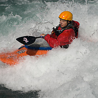 Kayaker Lianne Germaine plays in waves on the Kananaskis River in the Canadian Rockies near Calgary, Alberta.
