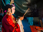 "30 JUNE 2016 - BANGKOK, THAILAND: A performer prays before going on stage for a Chinese opera performance at Chiao Eng Piao Shrine in Bangkok. Chinese opera was once very popular in Thailand, where it is called ""Ngiew."" It is usually performed in the Teochew language. Millions of Chinese emigrated to Thailand (then Siam) in the 18th and 19th centuries and brought their culture with them. Recently the popularity of ngiew has faded as people turn to performances of opera on DVD or movies. There are about 30 Chinese opera troupes left in Bangkok and its environs. They are especially busy during Chinese New Year and Chinese holidays when they travel from Chinese temple to Chinese temple performing on stages they put up in streets near the temple, sometimes sleeping on hammocks they sling under their stage.       PHOTO BY JACK KURTZ"