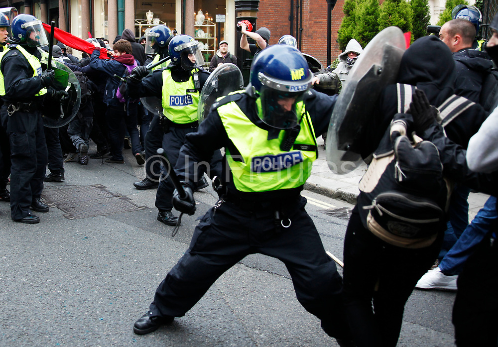 Protesters fight running battles with riot police, this time a clash in Mayfair. Anti capitalists / anarchists go on the rampage through central London on the back of the peaceful TUC protest march. The masked demonstrators ran a twisting route through the capital confusing the police and creating a situation which was very difficult to manage. The protesters attacked banks, shops and hotels, and the police in riot gear fought  face to face with them as they were pelted with ammonia, paint and fireworks loaded with coins.