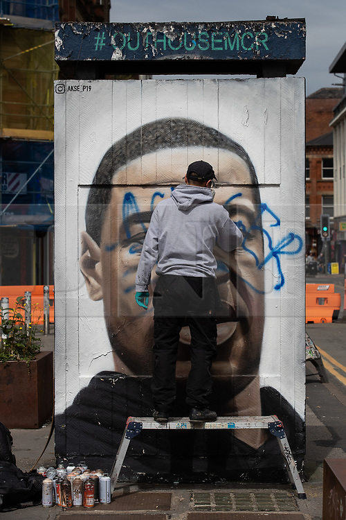 """© Licensed to London News Pictures . 22/07/2020 . Manchester , UK . A mural to George Floyd in the Northern Quarter of Manchester City Centre is repainted by the artist after it was sprayed with racist graffiti . """" Nigger """" was sprayed across the face of the artwork by Manchester artist AKSE overnight . Photo credit : Joel Goodman/LNP"""