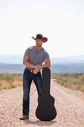 cowboy leaning on a guitar case on a dirt road