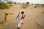 Tuareg man with camel in the desert around Timbuktu, in Mali.