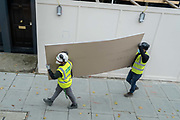Two workmen from a nearby construction site carry some sheets of plasterboard in Westminster, on 20th October 2020, in London, England.