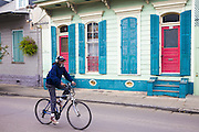 Cyclist passes bright color houses along Lower Bourbon Street in French Quarter of New Orleans, Louisiana, USA