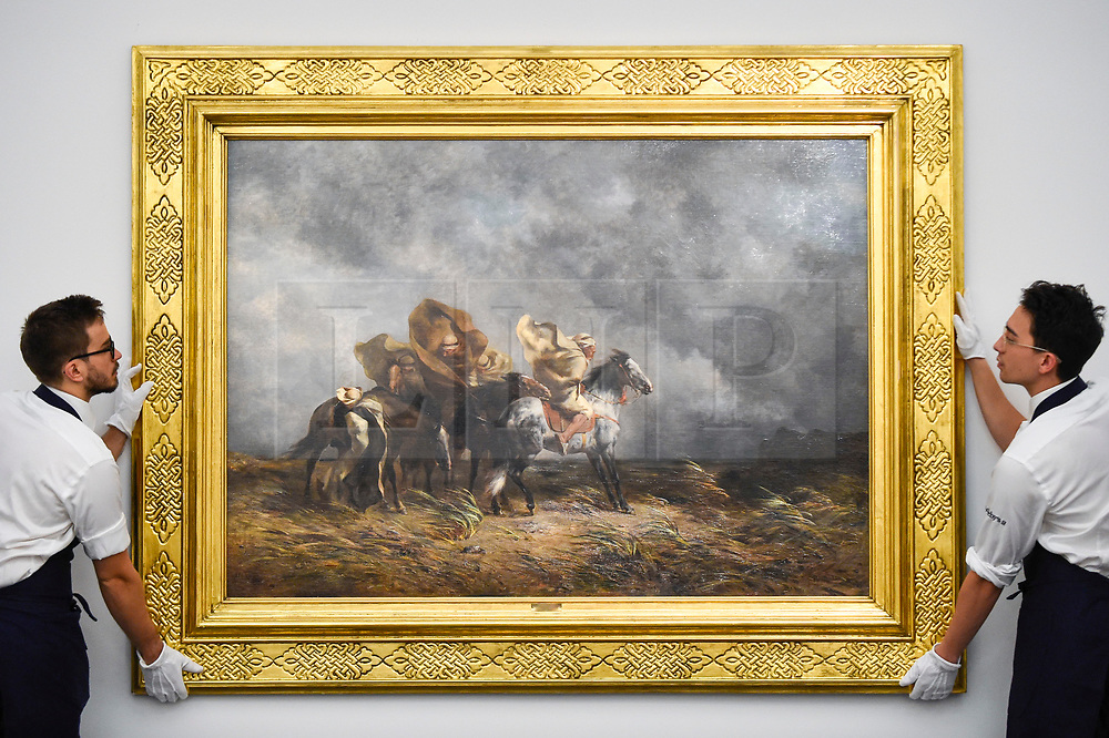 """© Licensed to London News Pictures. 11/10/2019. LONDON, UK. Technicians present """"Windstorm on the Esparto Plains of the Sahara"""", 1864, by Eugene Fromentin, (Est GBP400-600k).  Preview of works from the Najd Collection of orientalist paintings at Sotheby's in New Bond Street, which record daily life in the historic Arab, Ottoman and Islamic worlds  All 155 paintings are on public view 11- 15 October, with 40 works to be auctioned on 22 October.  Photo credit: Stephen Chung/LNP"""