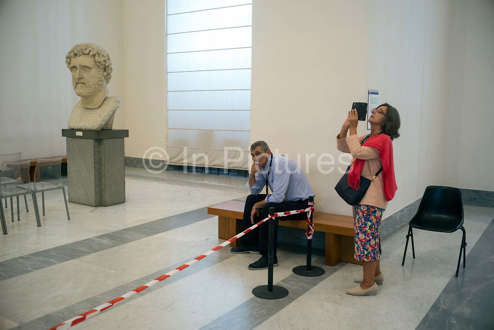 A woman takes a photograph whilst a bored guard rests in the National Archaeological Museum in Naples, Italy. The Museo Archeologico Nazionale di Napoli, MANN, formerly Real Museo Borbonico Bourbons Royal Museum is considered the most important Italian archaeological museum and one of the most important in the world for classical, and particularly ancient Roman, archaeology. Its collection includes works of the highest quality produced in Greek, Roman and Renaissance times and especially Roman artifacts from nearby Pompeii, Stabiae and Herculaneum.