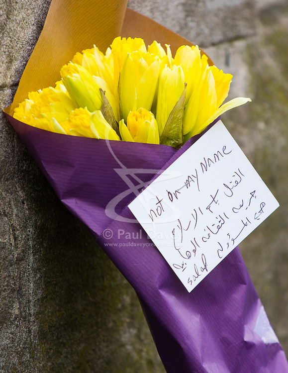 "Westminster, London, March 23rd 2017. Daffodils with a card written mainly in Arabic saying ""Not In My Name"" on Whitehall as investigations continue following Tuesday's terrorist attack on Westminster Bridge and in the grounds of Parliament, in which four people and their attacker were killed with over 40 injured."