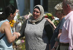 A woman is comforted after a minute's silence near to Grenfell Tower in west London following a fire which engulfed the 24-storey building on Wednesday morning.