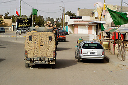 British soldiers wearing desert camouflage, Kevlar helmets and body armor, carrying SA80 assault rifles which are fitted with SUSAT sights,  travel in armored Land Rover patrol vehicles, also known as a snatch, to begin a foot patrol through a market area of Basra during Op-Telic in March 2005
