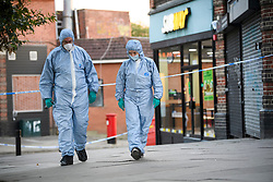 © Licensed to London News Pictures. 21/08/2018. London, UK. Police forensics outside Chicken Cottage on Rayners Lane, Harrow, north London, the scene of a double shooting. Armed police are reported to be searching the area after two men were shot in broad daylight. Their condition is unknown. This follows two separate shooting incidents in London yesterday. Photo credit: Ben Cawthra/LNP