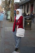 People from various ethnic backgrounds around the market on Whitechapel High Street in East London. This area in the Tower Hamlets is predominantly Muslim with just over 50% of Bangladeshi descent. This is known as a very Asian and multi cultural part of London's East End. School girl in Hijab uniform.