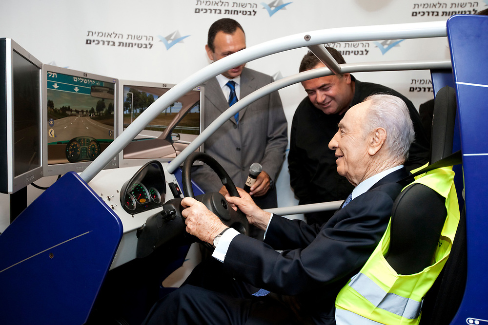 Israel's President Shimon Peres (R) operates a new driving simulator during his visit to the National Road Safety Authority headquarters in Jerusalem, on August 30 ,2011.