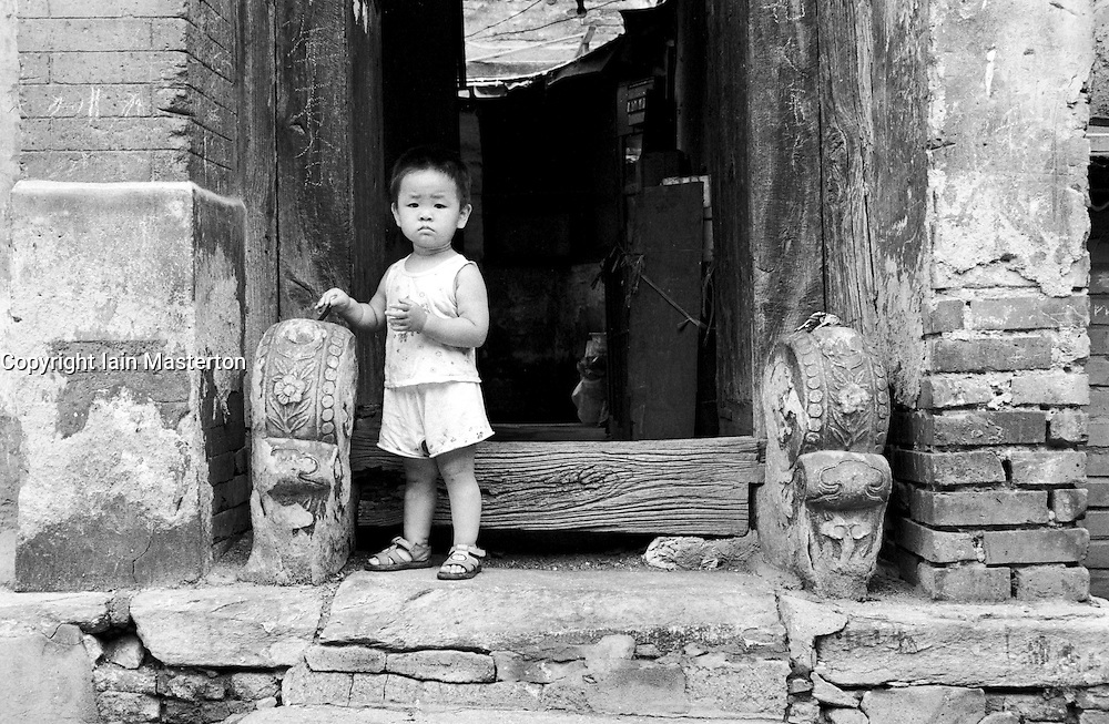 Child stands a front door of an old house in a Beijing hutong