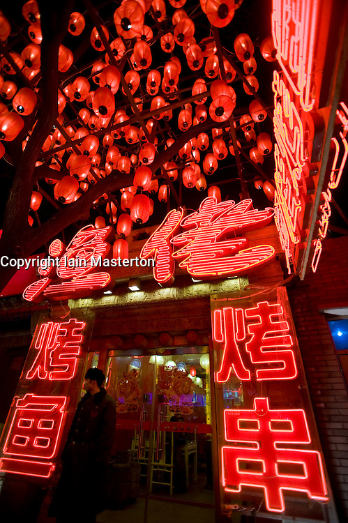 Many red lanterns and neon signs outside restaurant on street known ad Ghost Street in Dongzhimen in central Beijing China