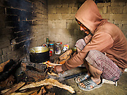 03 MARCH 2017 - BAGMATI, NEPAL: A worker in a brick factory in Bagmati, near Bhaktapur, starts the morning cooking fire in his home. There are almost 50 brick factories in the valley near Bagmati. The brick makers are very busy making bricks for the reconstruction of Kathmandu, Bhaktapur and other cities in the Kathmandu valley that were badly damaged by the 2015 Nepal Earthquake. The brick factories have been in the Bagmati area for centuries because the local clay is a popular raw material for the bricks. Most of the workers in the brick factories are migrant workers from southern Nepal. Most of the workers live at the factories, in homes made of stacked but not mortared, bricks.       PHOTO BY JACK KURTZ