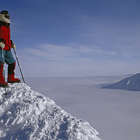 Lomonosov Icecap, Spitsbergen Island, Svalbard, Norway.A polar explorer stands atop a mountain surrounded by huge glaciers.