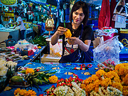08 JUNE 2017 - BANGKOK, THAILAND: A flower vendor in Khlong Toey Market, Bangkok's main fresh market. Thai consumer confidence dropped for the first time in six months in May following a pair of bombings in Bangkok, low commodity prices paid to farmers and a sharp rise in the value of the Thai Baht versus the US Dollar and the EU Euro. The Baht is surging because of political uncertainty, related to Donald Trump, in the US and Europe. The Baht's rise is being blamed for a drop in Thai exports. This week the Baht has been trading at around 33.90 Baht to $1US, it's highest point in two years.      PHOTO BY JACK KURTZ