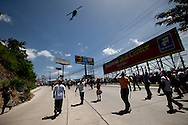 4 July 2009 - Tegucigalpa, Honduras - A military helicopter flys over supporters of ousted Honduras' President Manuel Zelaya during a protest march near the airport in Tegucigalpa, capital of Honduras. President Zelaya has stated that he will return tomorrow to challenge the government that overthrew him setting the stage for a dramatic standoff. His supporters have been marching in the capital's streets since he was ousted last Sunday.