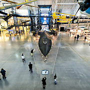 The main Boeing Hall, seen from an elevated vantage point, at the Smithsonian National Air and Space Museum's Udvar-Hazy Center, a large hangar facility at Chantilly, Virginia, next to Dulles Airport and just outside Washington DC. At the center of frame is the Lockheed SR-71 Blackbird supersonic spy plane. In the distance, behind it, is NASA's space shuttle Enterprise. Other planes are suspended from the roof.
