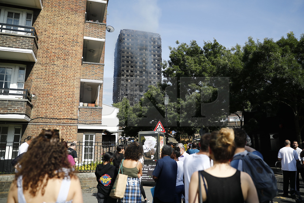 © Licensed to London News Pictures. 14/06/2017. London, UK. People watch as firefighters try to control the Grenfell Tower fire in west London on 14 June 2017. Photo credit: Tolga Akmen/LNP